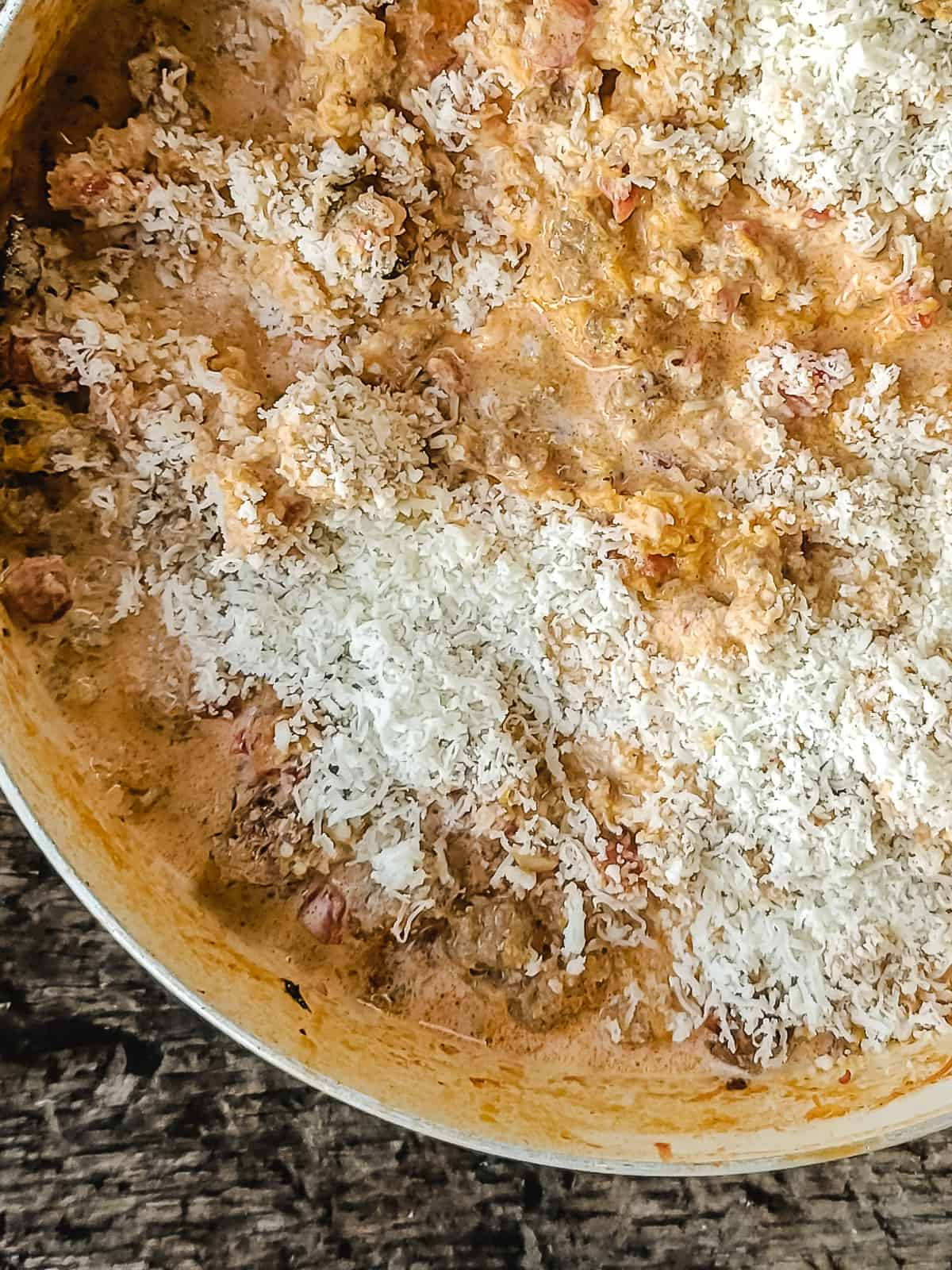 Creamy tomato sauce with ground sausage, sprinkled with Parmesan cheese.