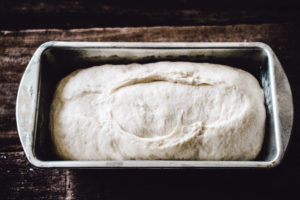 Homemade white bread dough in loaf pan with split top ready to be baked