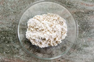 Glass bowl with crumbly pastry mixture.