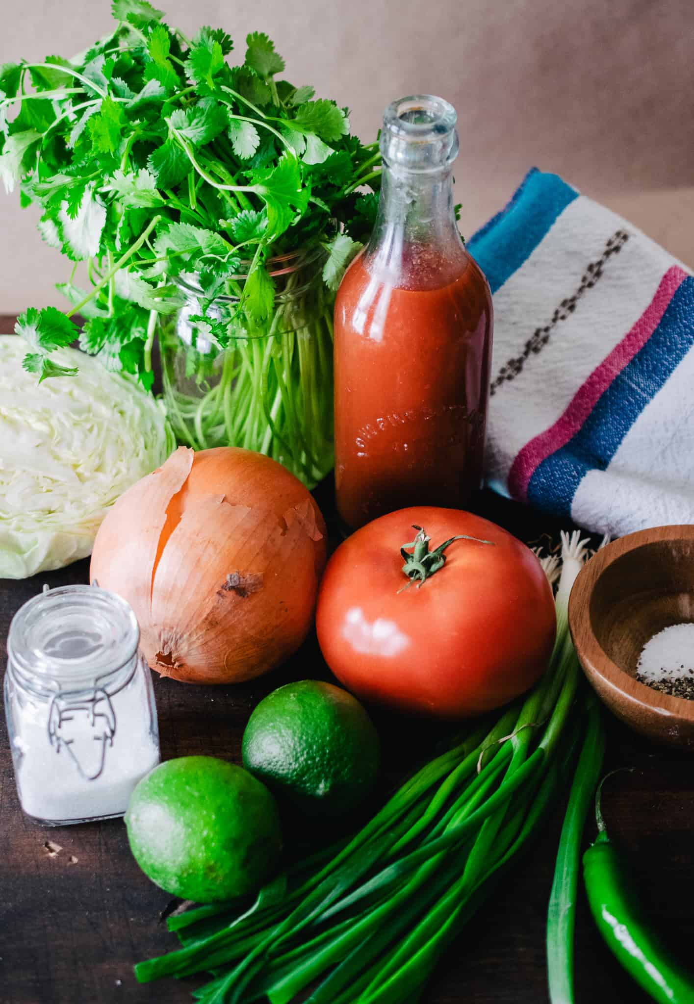 ingredients for homemade pico de gallo with cabbage on wooden surface with Mexican hand woven kitchen towel