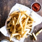 bowl of french fries on wooden table with salt and ketchup ramekin