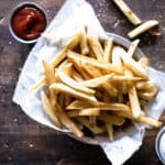 metal bowl lined with white parchment paper filled with french fries on wooden surface with ramekins of ketchup and salt
