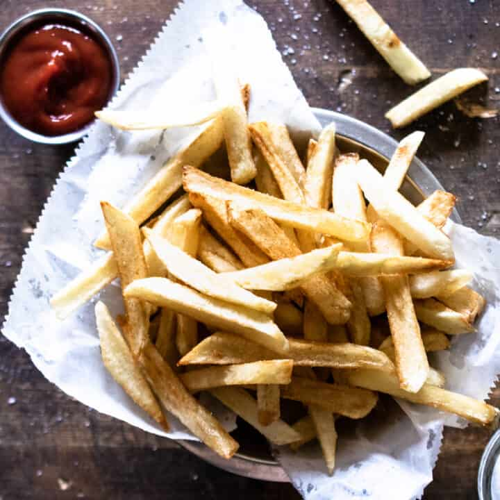 stainless steel bowl lined with white paper filled with golden crispy homemade french fries with ramekin of ketchup on wooden surface
