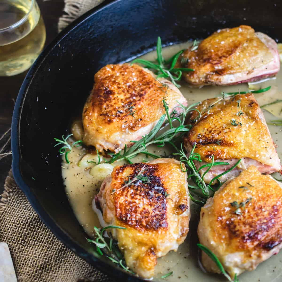 Skin on chicken with salt, herbs and a pan sauce in a cast iron skillet.