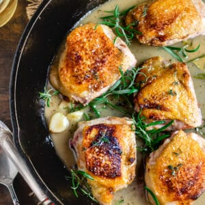 Seared chicken thighs in a cast iron pan with fresh herb sprigs and sauce.