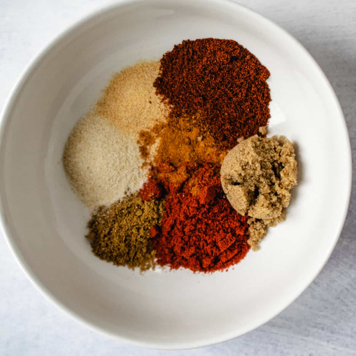 White bowl filled with seasonings and spices for making chili mix at home.