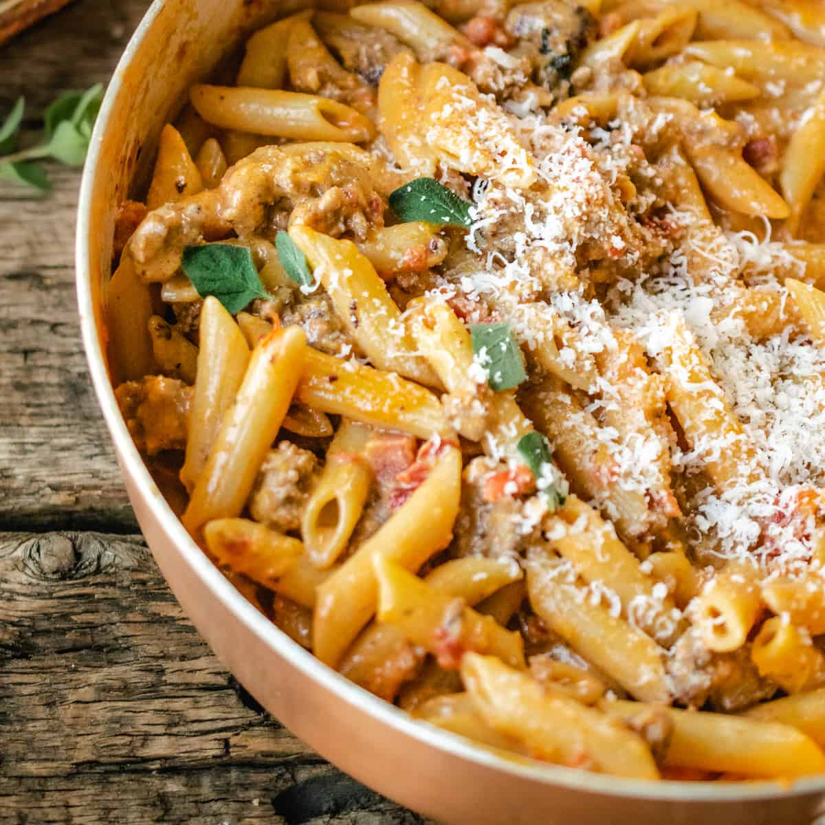 A skillet of penne pasta with vodka sauce, sausage and parmesan cheese on a rustic wooden back drop.