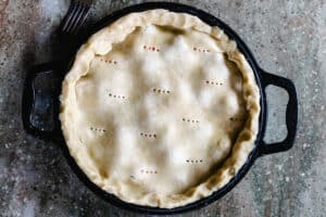 Cast iron pie pan with handles holding uncooked pie with holes poked in the top.