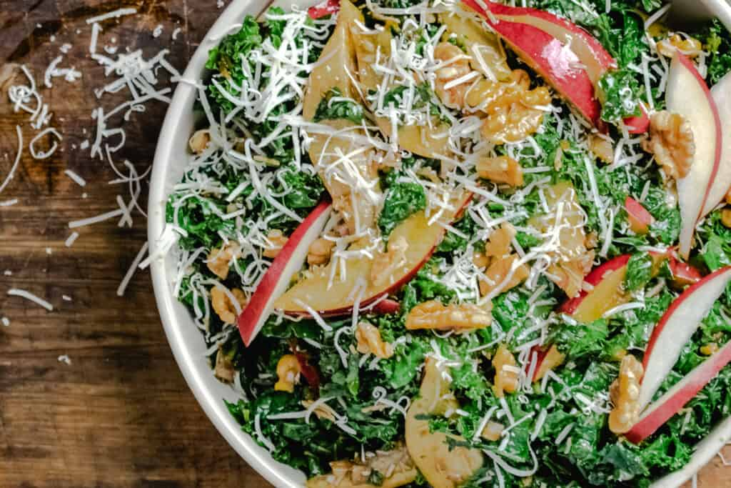 Bowl of tossed greens with red pears and walnuts.