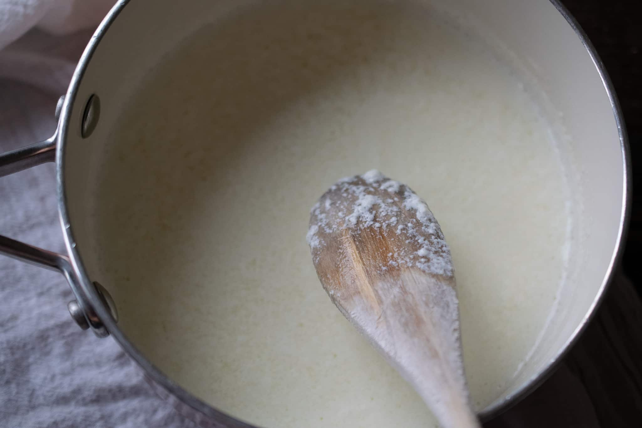 pot of heated milk and cream with vinegar stirred in to curdle for ricotta cheese