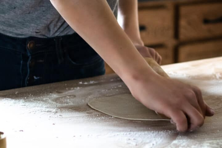 woman rolling out homemade tortillas on floured butcher block surface