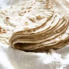 Stack of homemade flour tortillas folded in half on white cloth