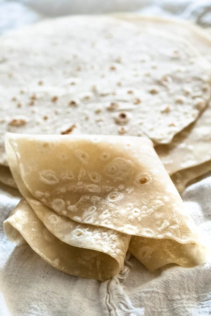 homemade flour tortilla folded into quarters to show flexibility on white cloth
