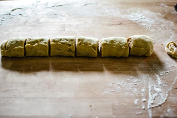 uncooked rolled log of cinnamon roll cut into 6 equal rolls ready to be placed in pan on a floured wooden surface