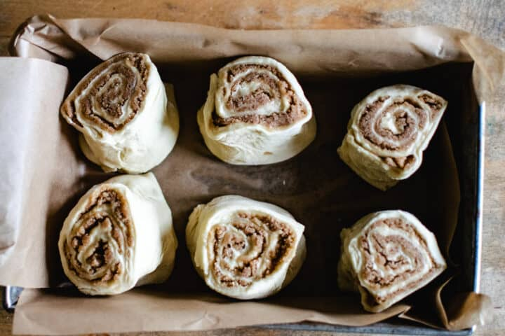 six uncooked homemade cinnamon rolls in a brown parchment paper lined pan, ready for second rise