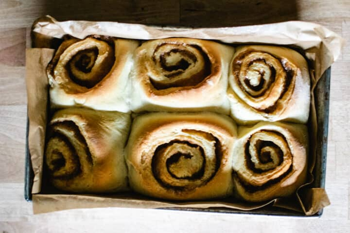 rectangular metal pan, lined with brown parchment paper, with six homemade cinnamon rolls on wooden surface
