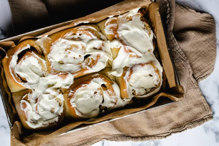 rectangular metal pan with brown parchment paper holding 6 jumbo cinnamon rolls with frosting on marble surface