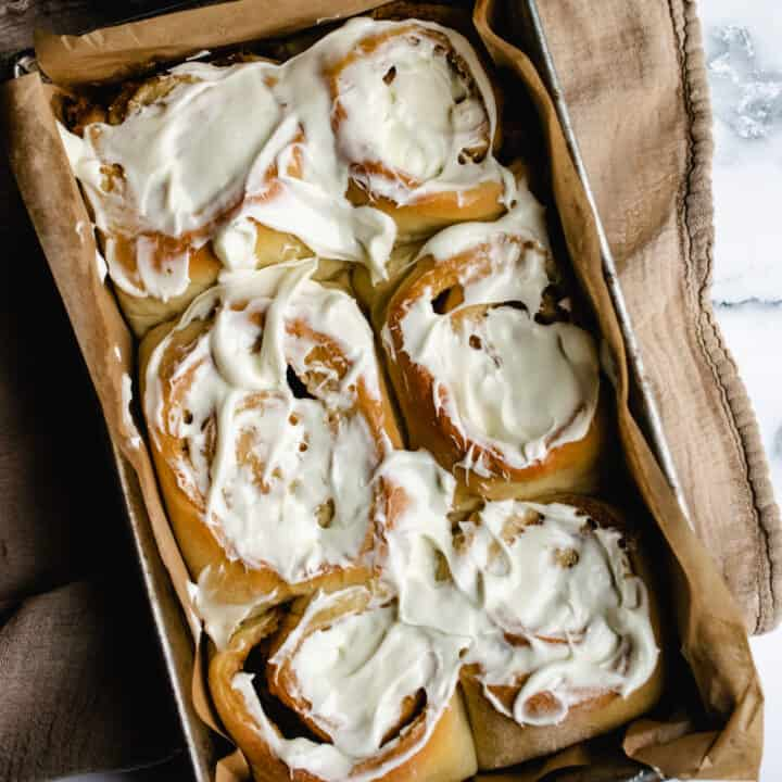 pan of six jumbo cinnamon rolls with cream cheese frosting on brown muslin towel
