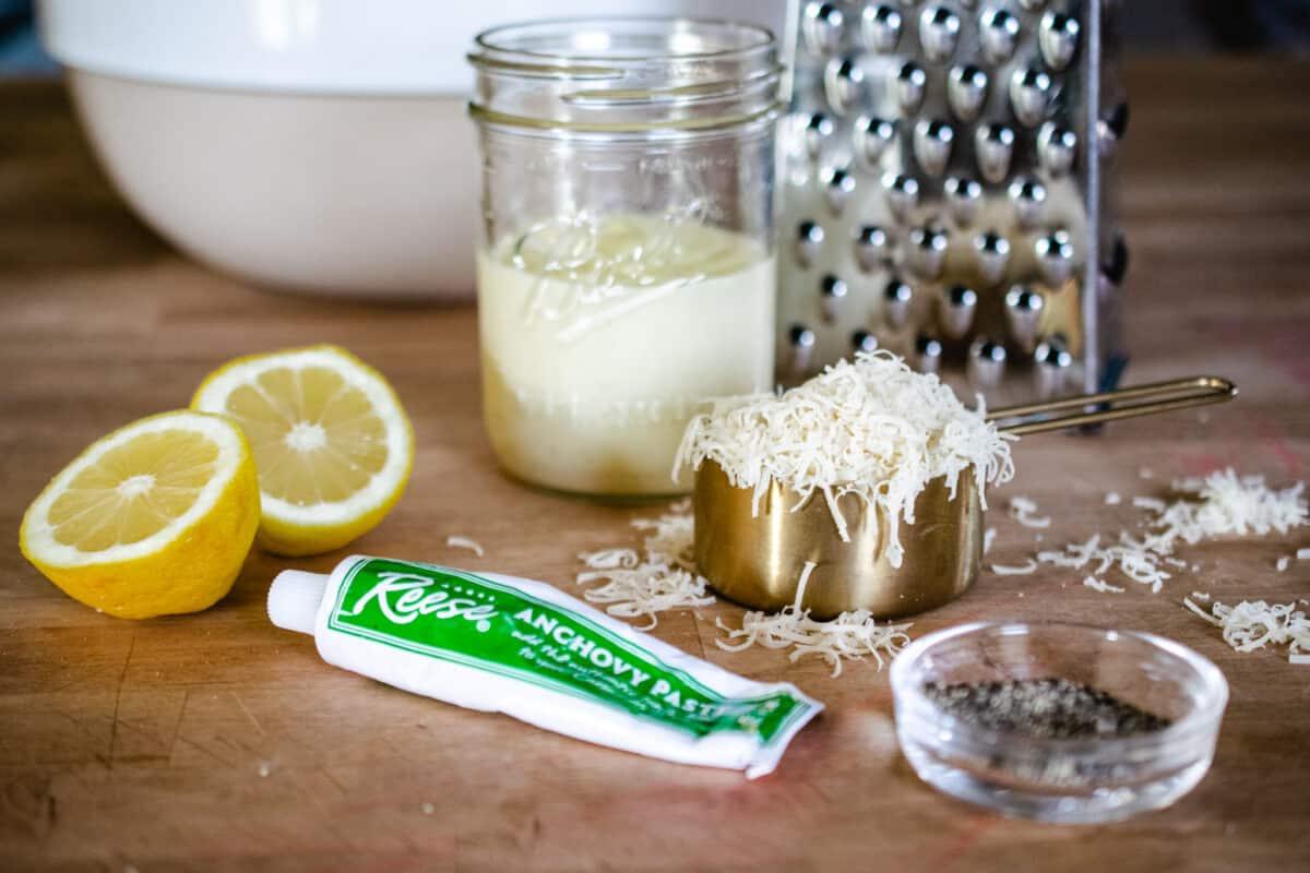 ingredients for homemade caesar salad including lemon, tube of anchovy paste, cup of shredded Parmesan, black pepper on wood butcher block