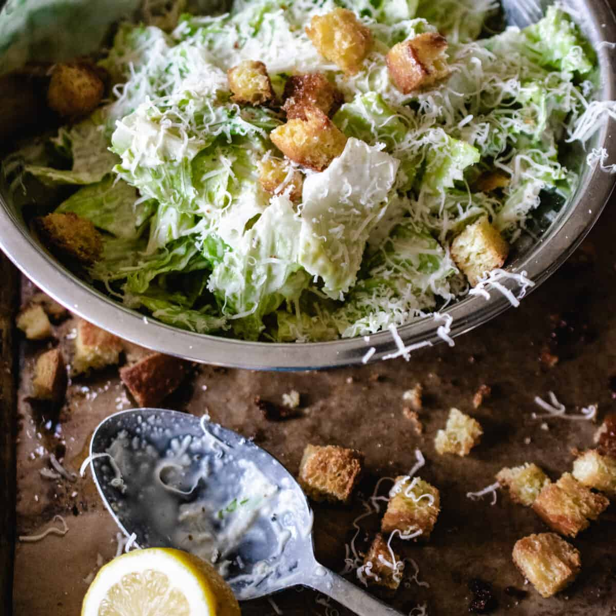 stainless steel bowl of tossed Caesar salad, with croutons, lemon wedge and spoon