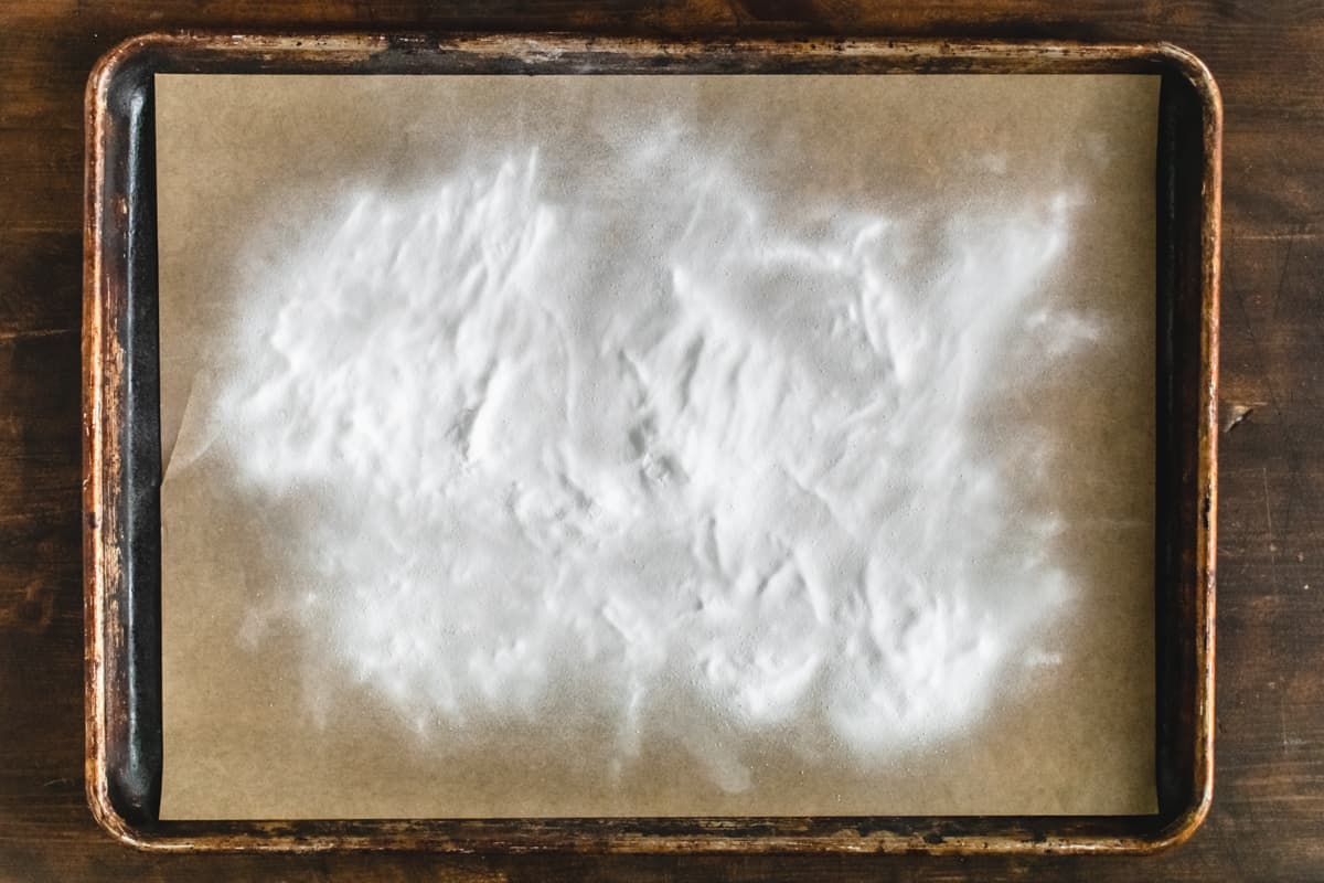 Baking soda sprinkled on parchment paper on a baking sheet.
