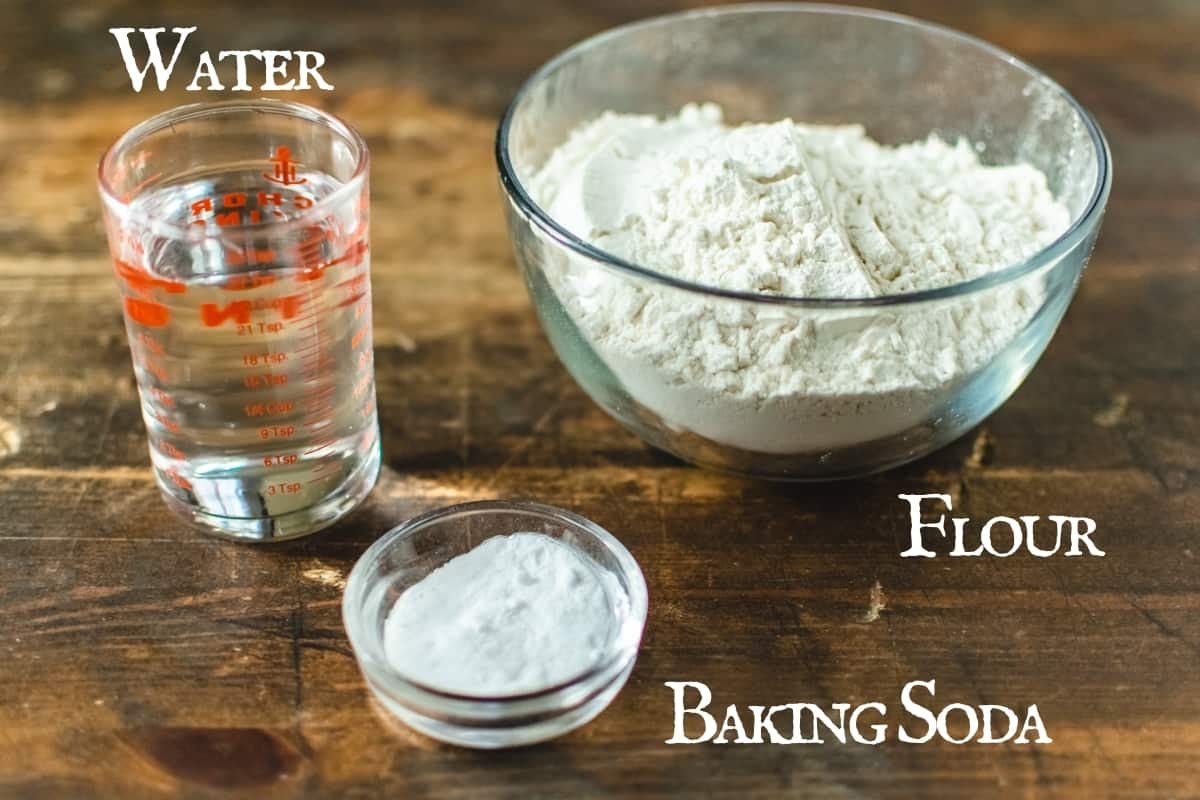 A bowl of flour, baking soda and cup of water on wooden surface.