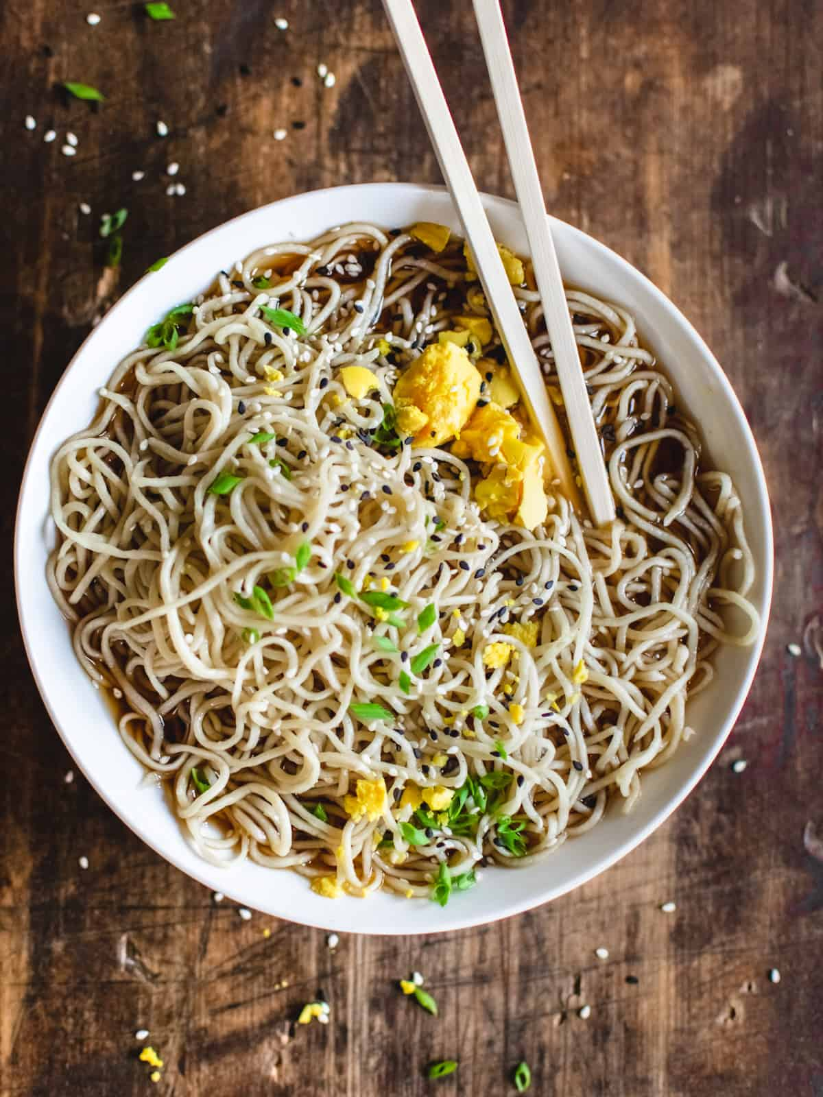 Bowl of ramen noodles in broth with egg yolk, scallions, sesame seeds and chopsticks.