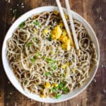 A bowl of ramen noodles in broth with scallions, egg yolk, and sesame seeds with chopsticks.
