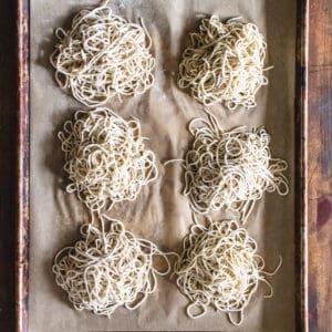 Piles of ramen noodles on parchment paper.