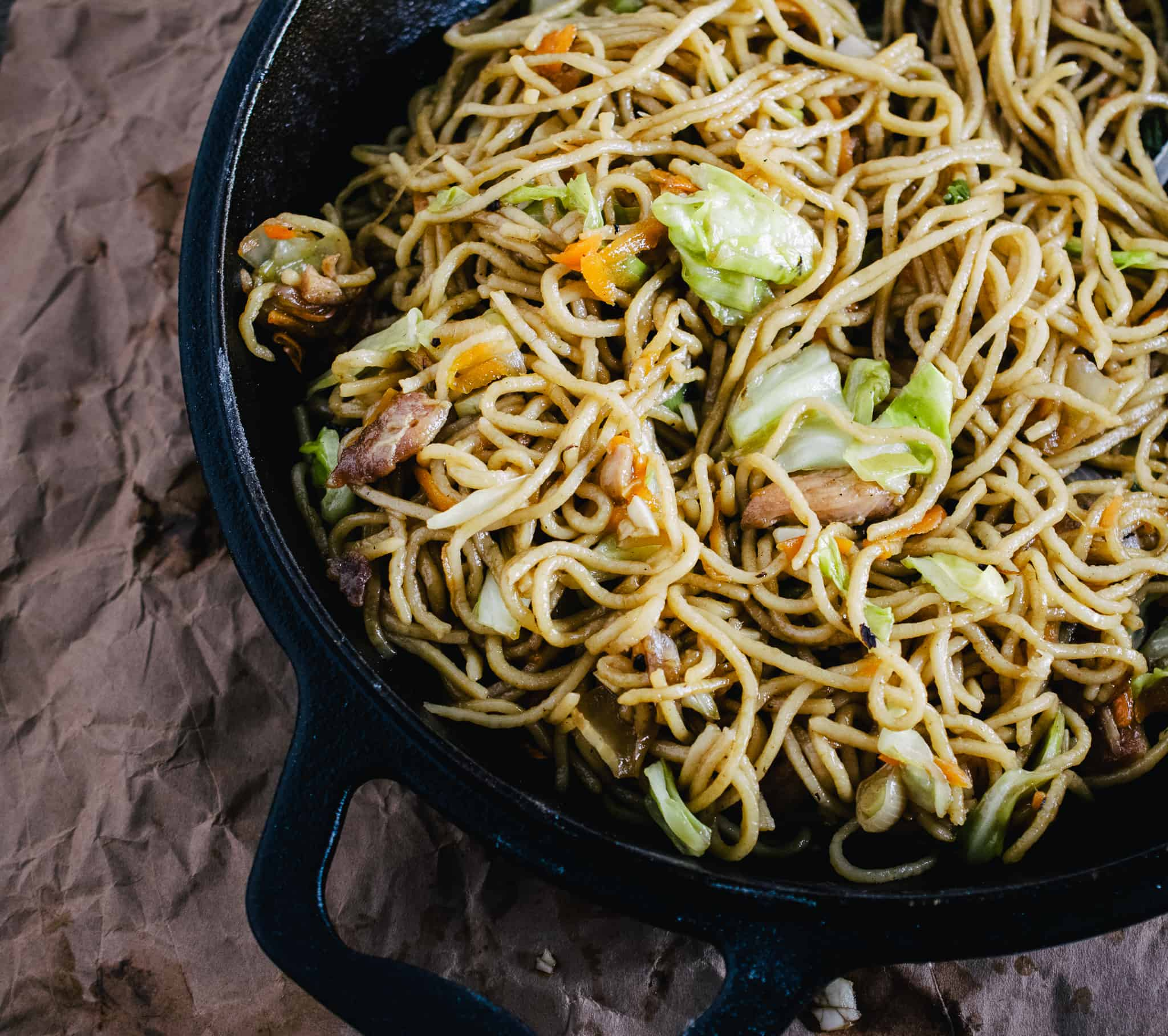black iron skillet with stir fry noodles on brown crinkled paper