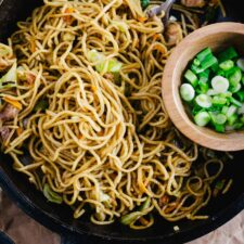 iron skillet with stir fry noodles and wooden bowl of scallions on brown paper