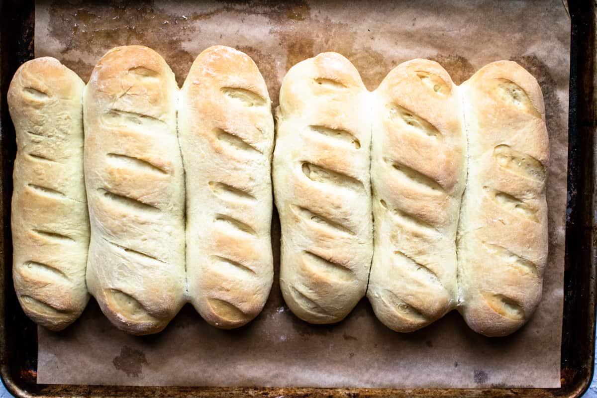 Six baked hoagie rolls on a baking sheet.