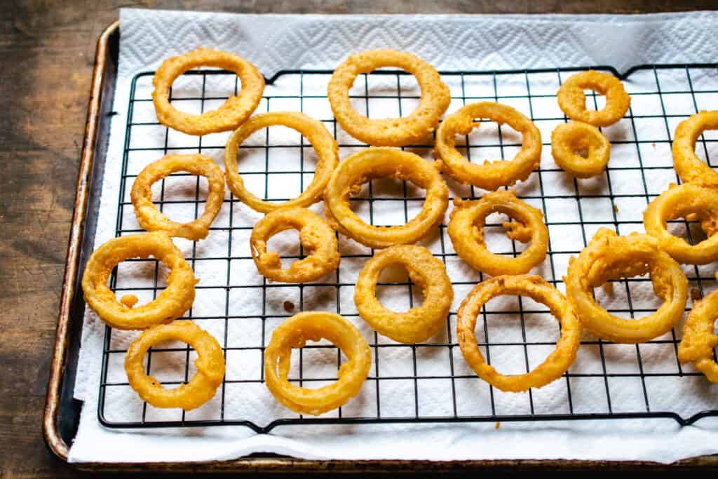Fried onion rings on a black wire rack over paper towels on a baking sheet.