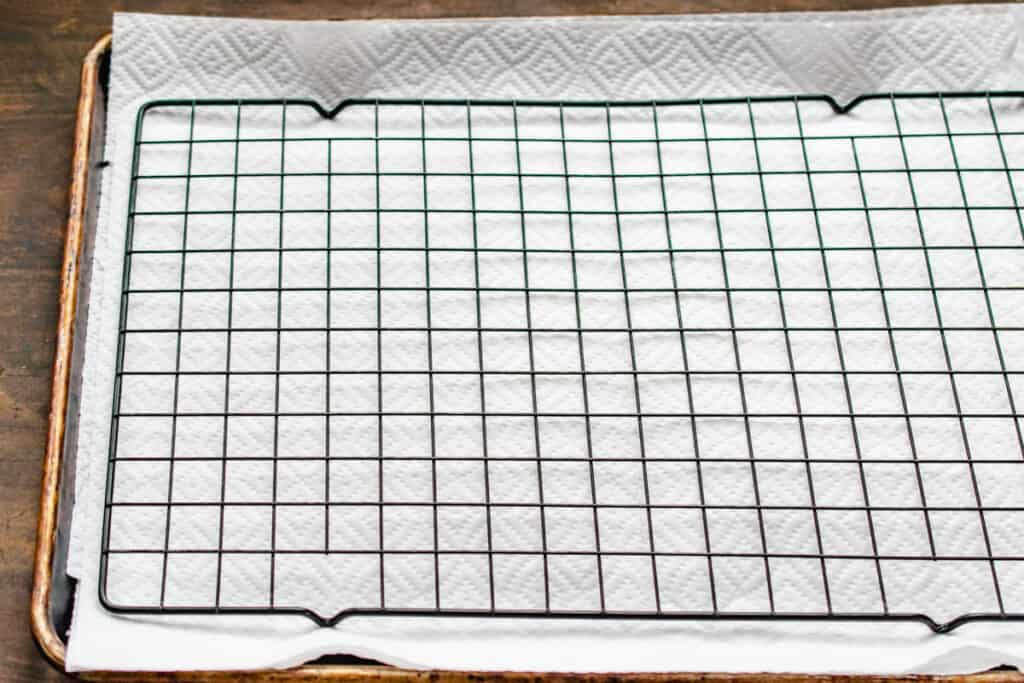 Black cooling rack laid over paper towels and a baking tray.