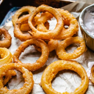 Breaded, fried onion rings on parchment paper with dipping sauce.