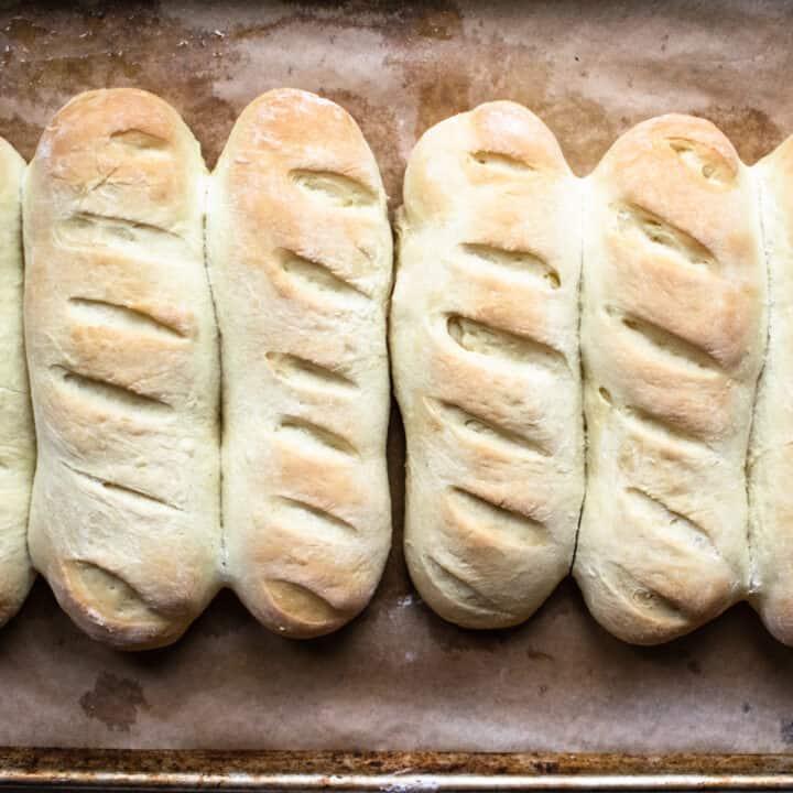 Hoagie bun rolls lined up on a baking sheet.