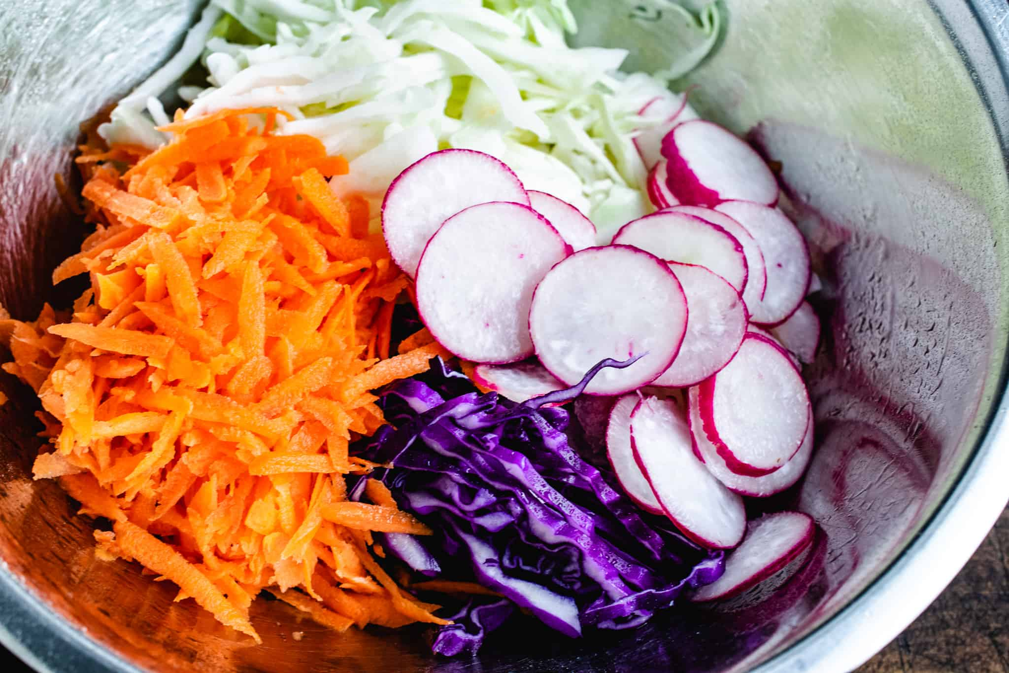 metal bowl of shredded carrots, red and green cabbage, and sliced radish for slaw