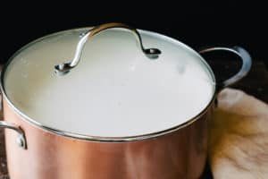 copper pot with lid on it full of coagulated milk for making mozzarella cheese process