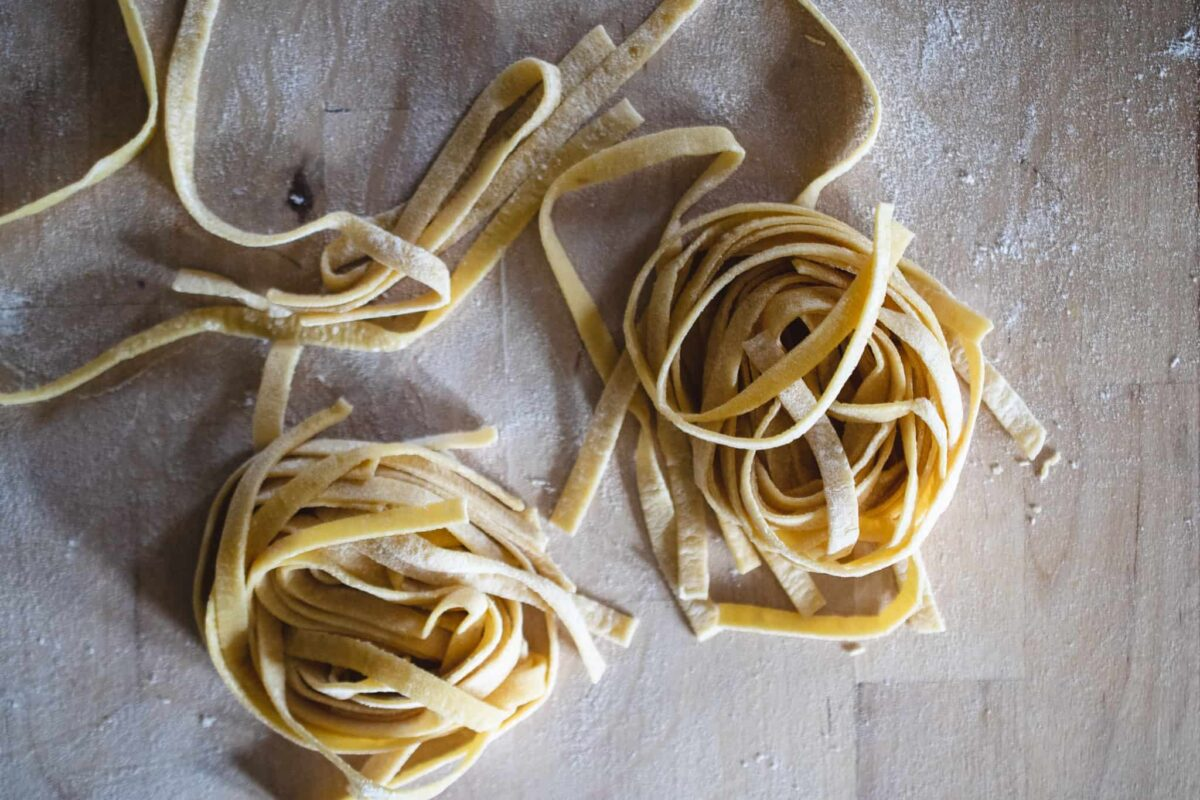 two homemade fettuccine pasta ribbons in nests on floured wood butcher block surface