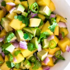diced mango, avocado, red onion, Serrano pepper and cilantro tossed in lime juice in a white bowl