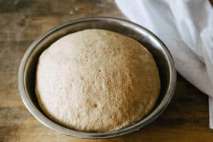 bread dough that has doubled in size in a greased metal bowl on a wooden table with flour sack cloth next to it