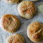 freshly baked split top and sesame seed hamburger buns on a parchment paper lined baking sheet