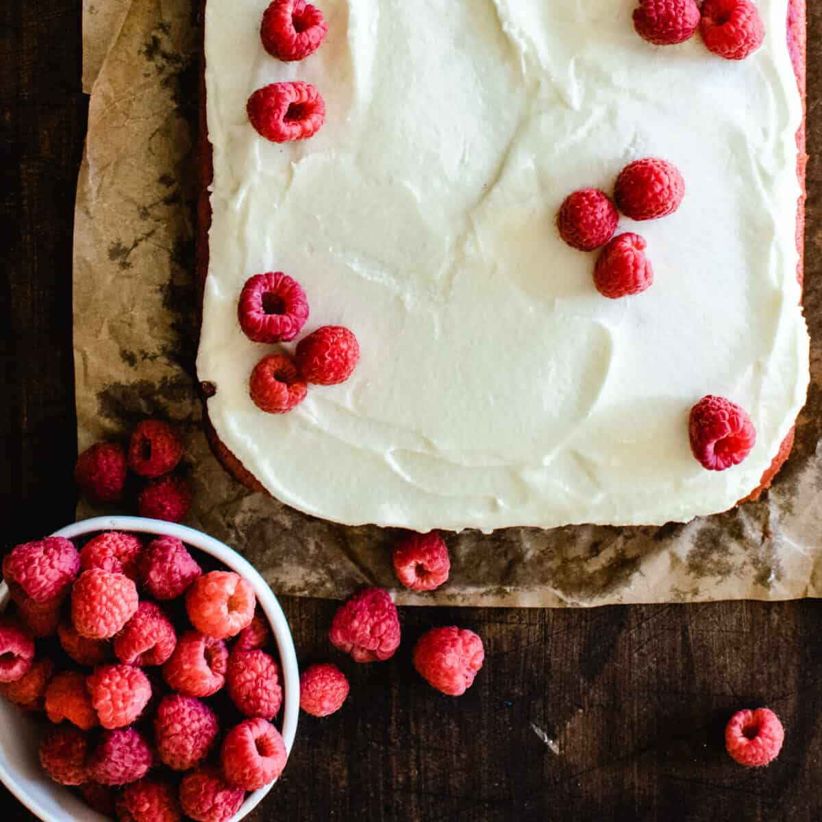raspberry sheet cake on brown parchment paper with white frosting and bowl of fresh raspberries to decorate the top