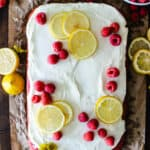 raspberry sheet cake on parchment paper topped with white frosting and fresh lemon slices and raspberries