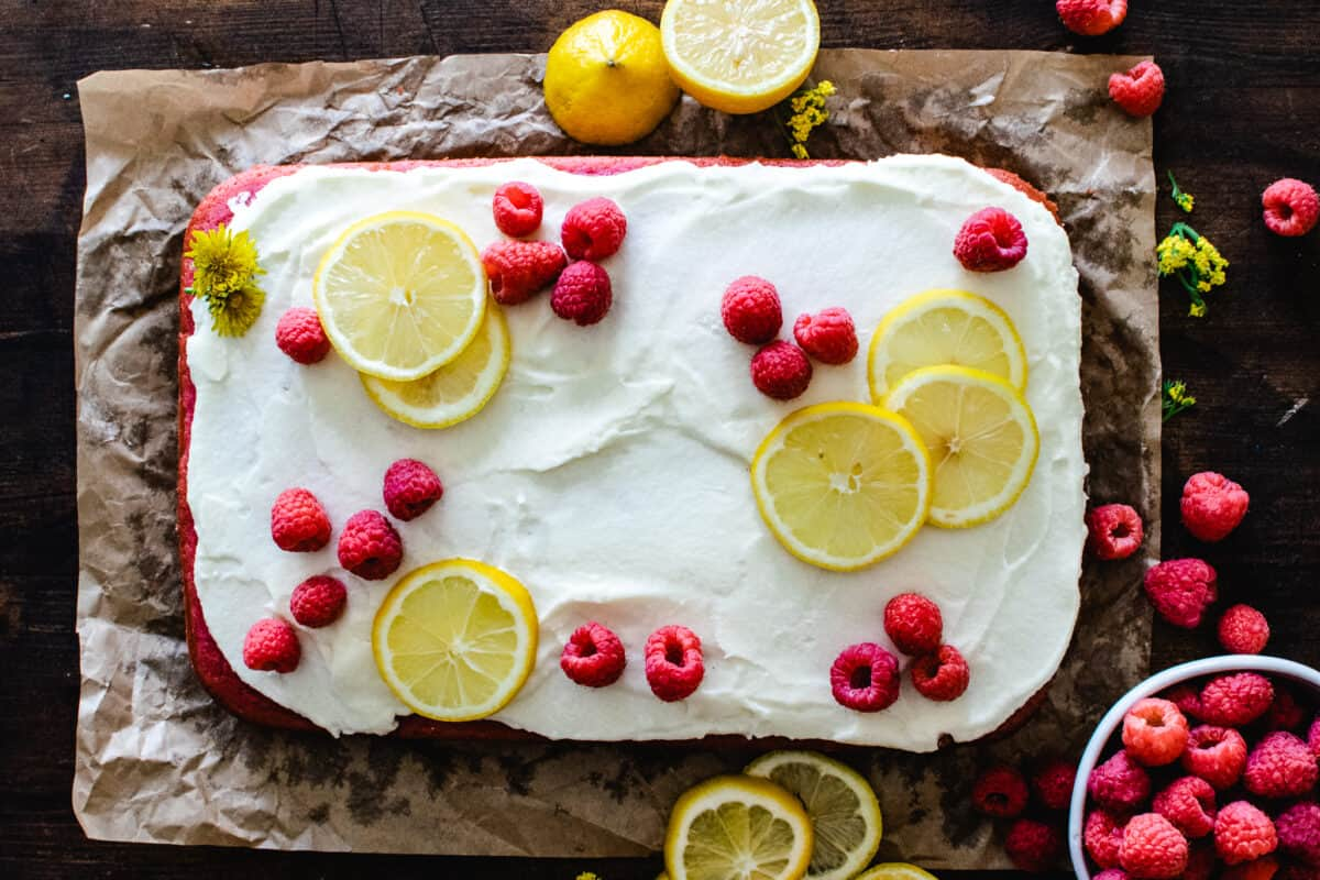 raspberry sheet cake with white frosting and fresh raspberries and lemon slices on brown parchment paper