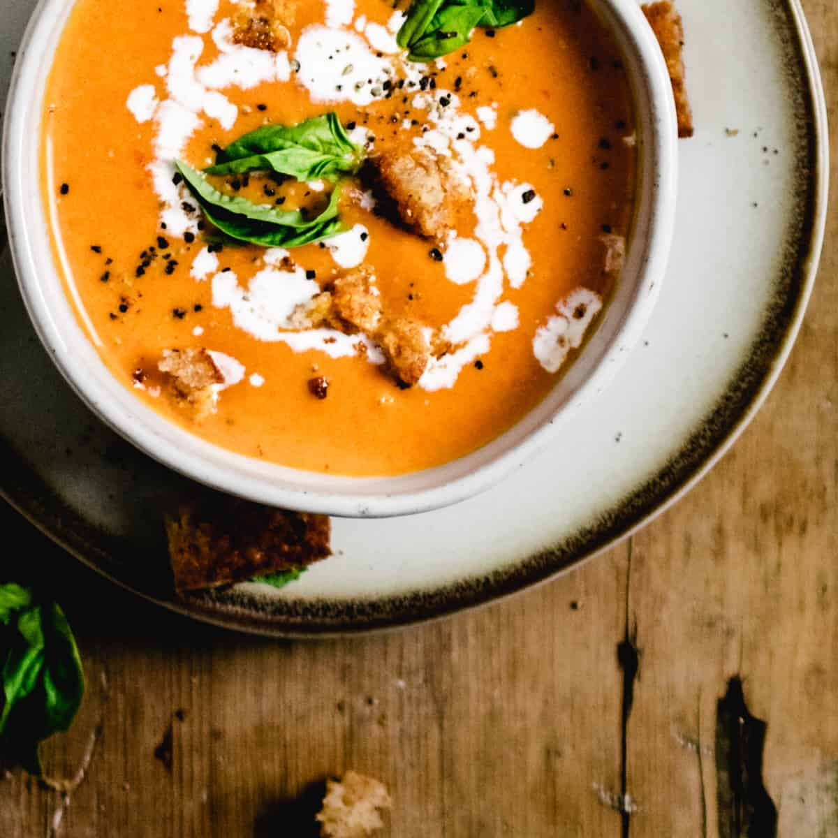 Bowl of tomato soup topped with fresh basil leaves and swirl of cream on plate and wooden board.