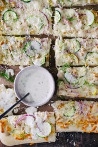 sliced homemade chicken ranch pizza with red onion and zucchini with ramekin of ranch dressing and fresh dill