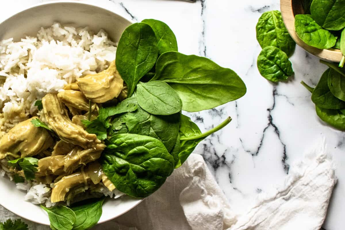 bowl of chicken curry and basmati rice served with a bed of fresh spinach leaves in a white bowl next to white napkin on marble counter and wooden bowl of extra fresh spinach