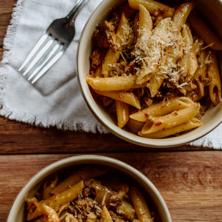 Penne shaped pasta with Parmesan cheese and red sauce in two bowls.