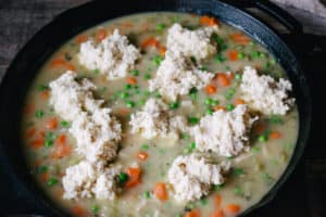 raw biscuit dumpling dough dropped into creamy chicken and vegetable soup in cast iron skillet for chicken and dumplings
